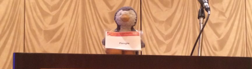 """a small stuffed penguin toy sits on top of a CCCC podium. It wears a name badge with the name """"Pengie"""" printed."""